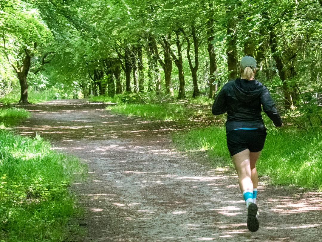 Michelle running along a tree-lined path